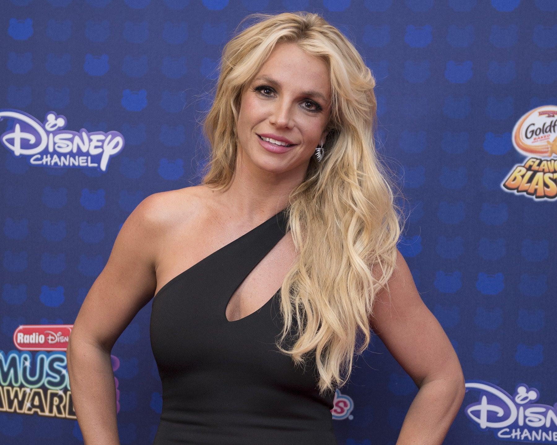 Britney smiles in a black one shoulder dress