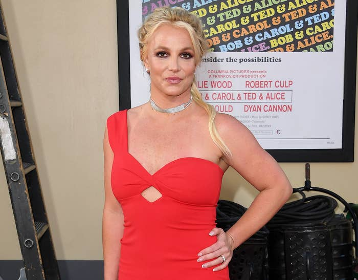 Britney poses with her hand on her hip while wearing a red one-shoulder dress