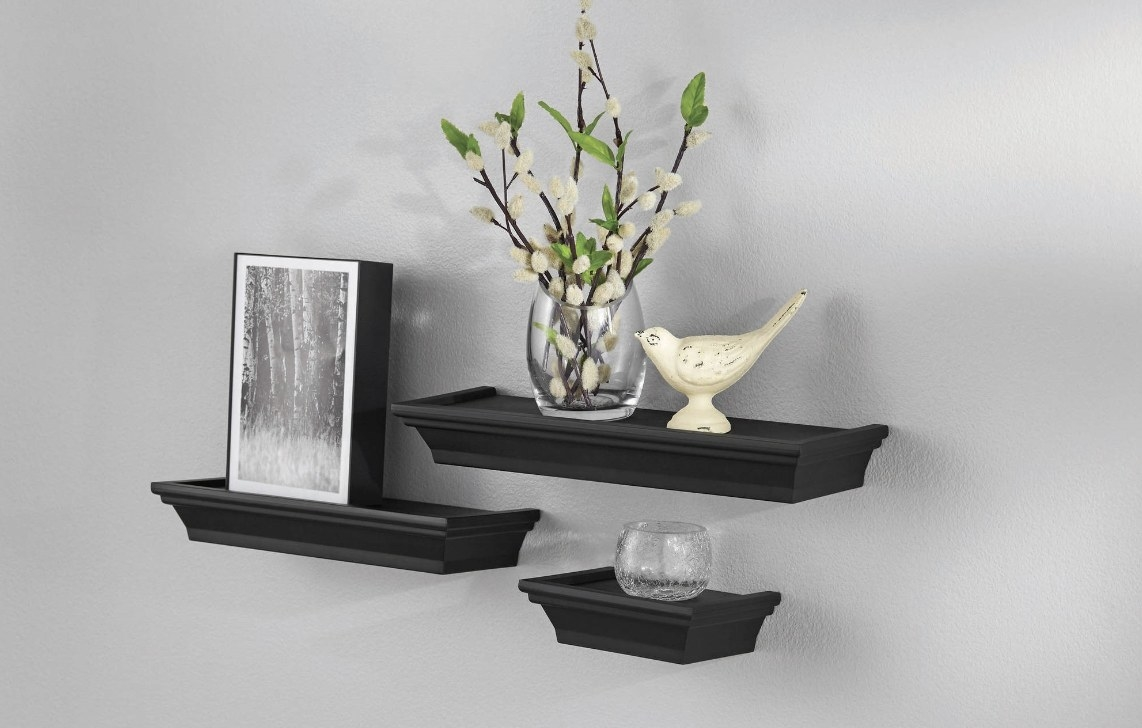 The black shelves have three various sizes and are holding various small items