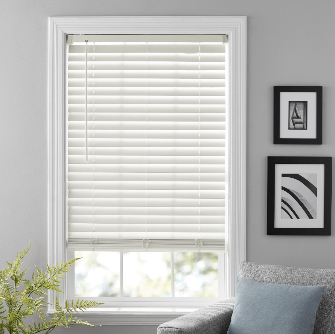 The white blinds are covering a window 3/4 of the way in a sunlit room
