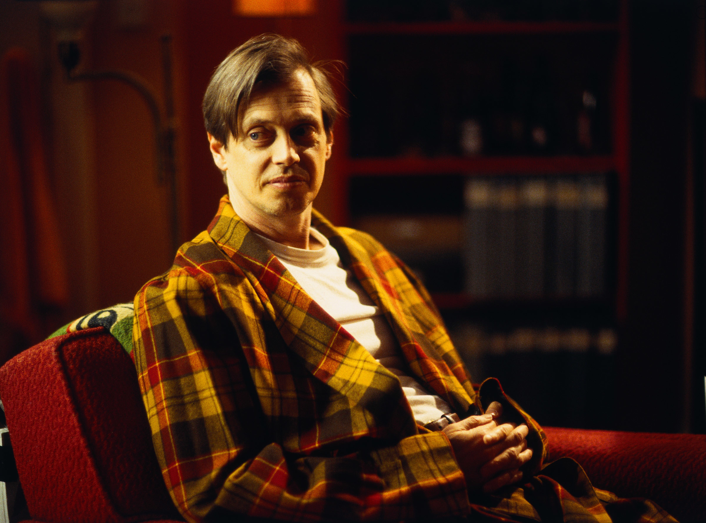Buscemi sitting on a couch in a bland robe in ghost world