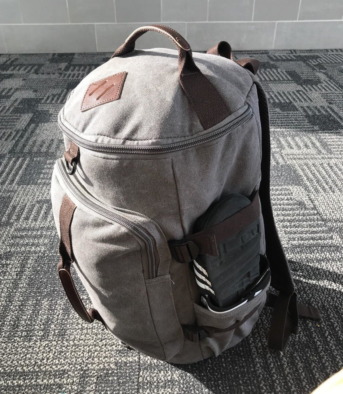 Reviewer photo of a grey canvas backpack with a bucket-style pocket, front pocket, and a side pocket holding sandals
