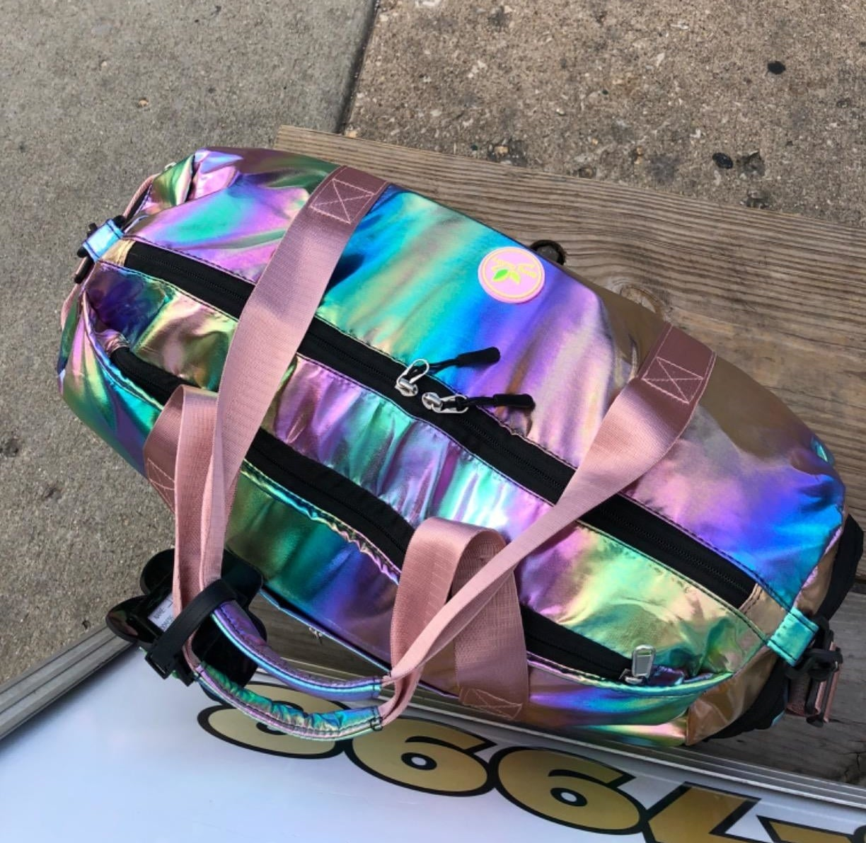 Reviewer photo of an iridescent duffel bag with pink nylon straps