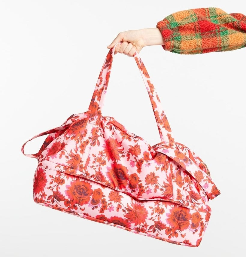 Model is holding a pink and red floral weekender bag with a bottom compartment for shoes