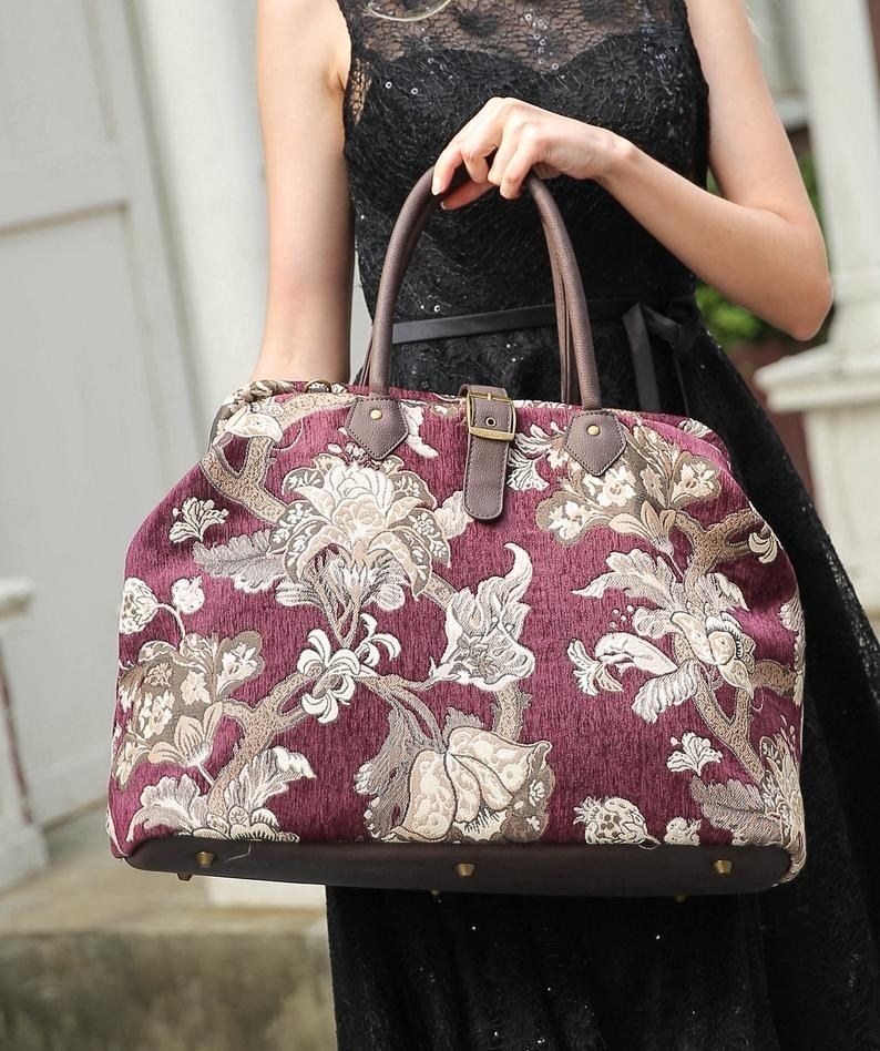 Model is holding a red Victorian-style bag with a beige floral pattern on it