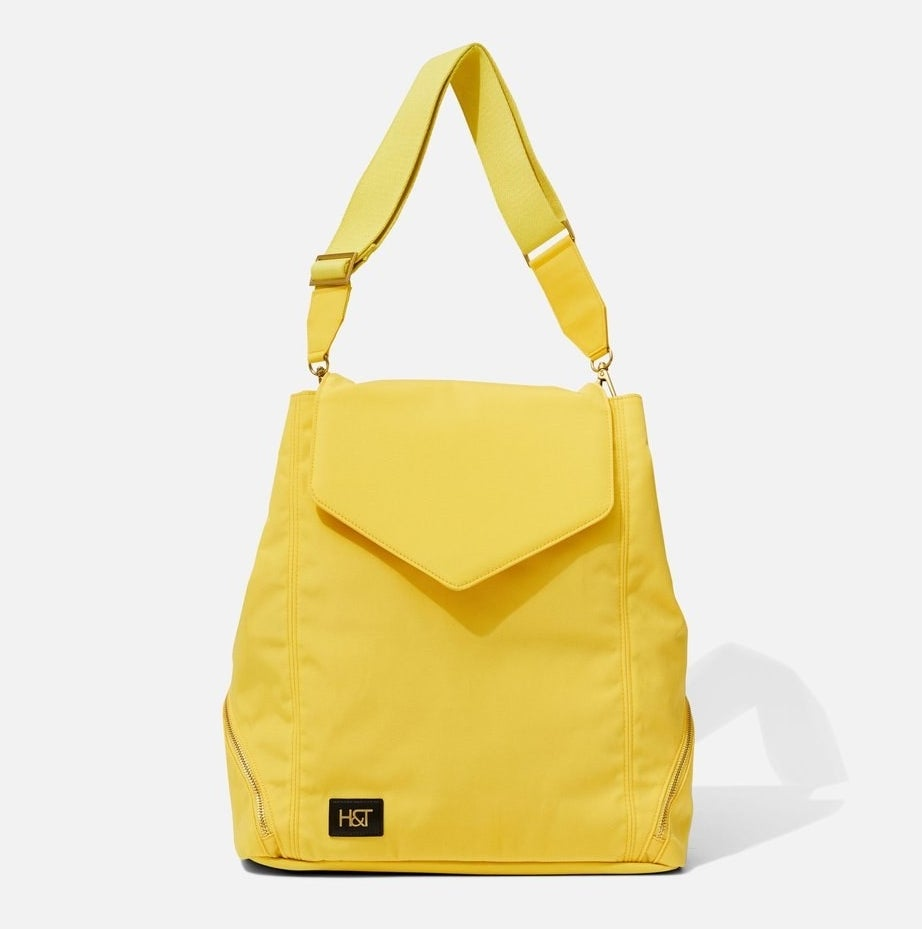 A yellow nylon backpack with two side zippers revealing a hidden shoe compartment