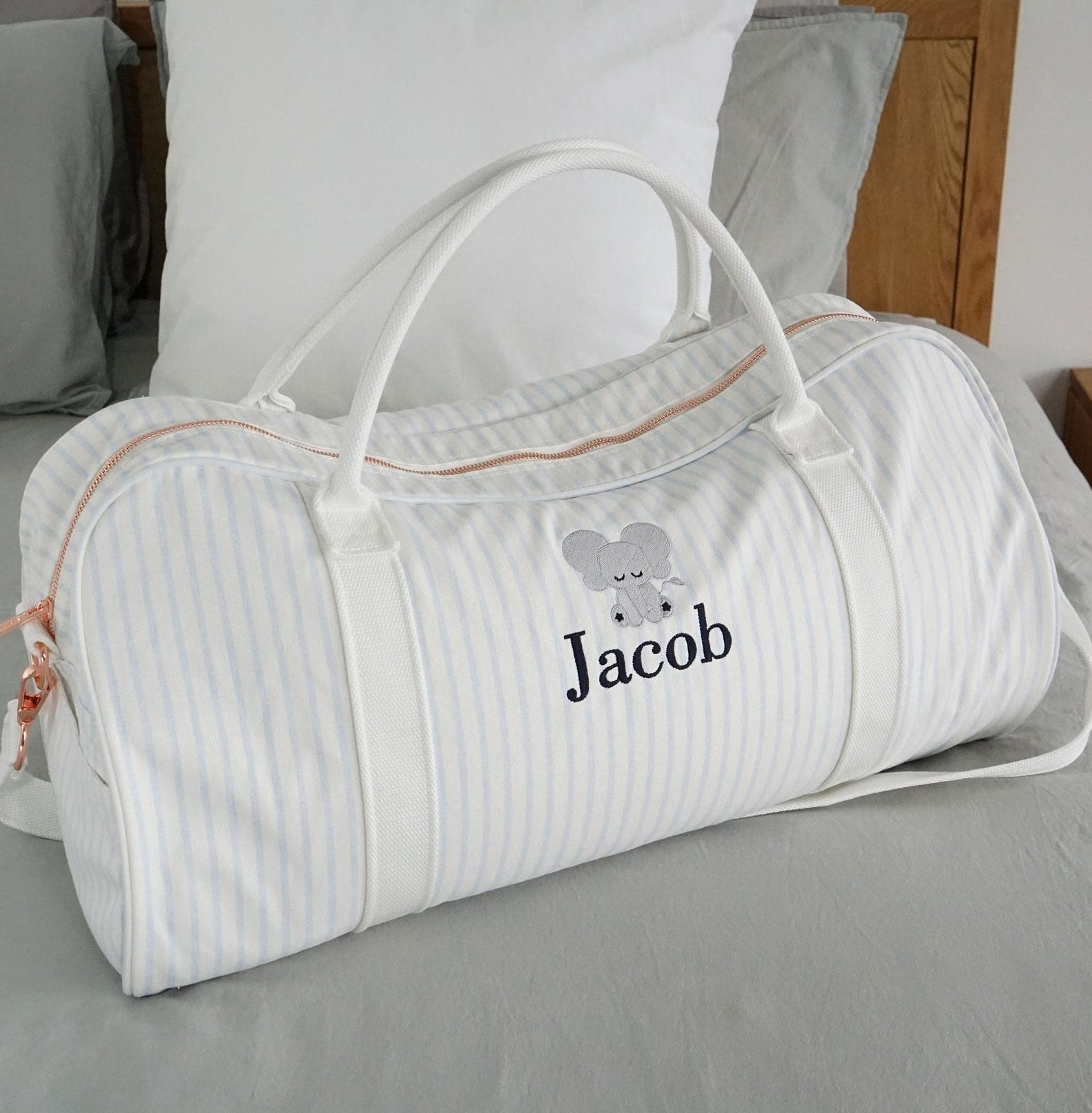 A white duffel bag with baby blue vertical stripes throughout and the name Jacob with a tiny elephant on the front
