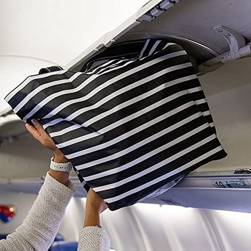 Model is putting a black and white striped tote into a overhead bin in a plane