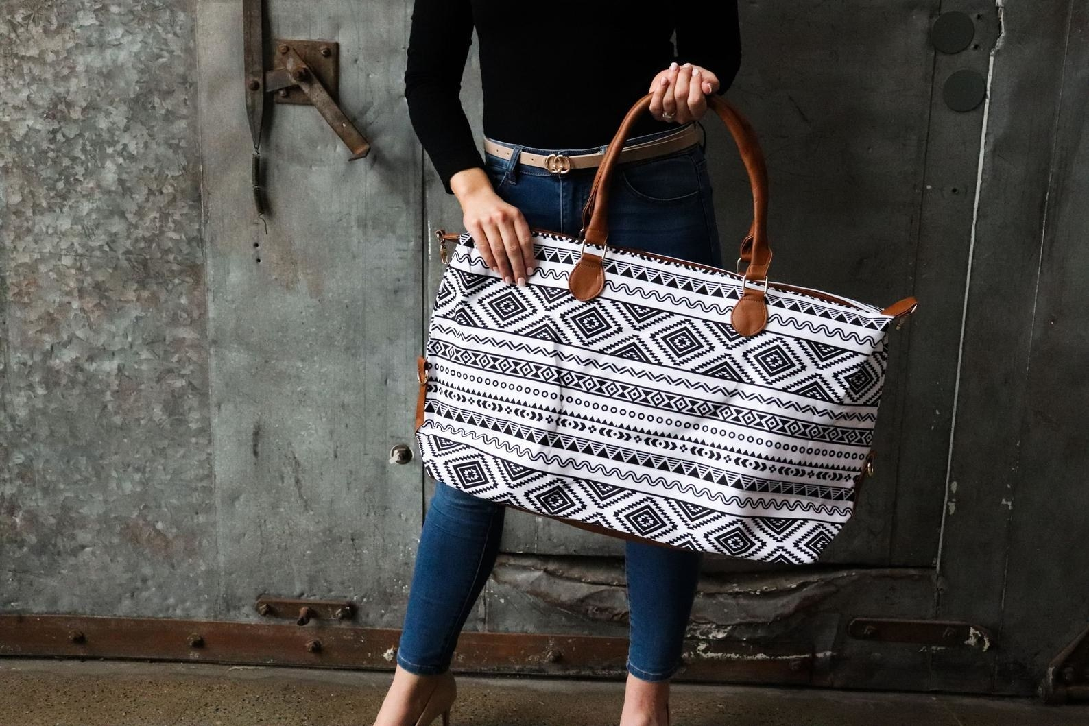 Model is holding a white and black geometric patterned tote with brown leather straps