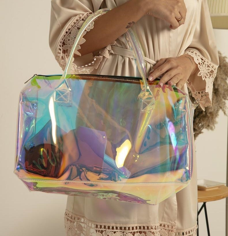 Model is holding a clear bag with a rainbow iridescent hue to it