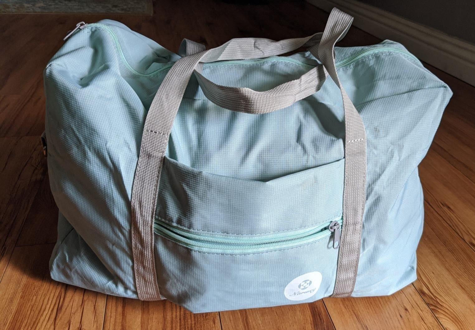 Reviewer photo of the light blue bag with a front pocket and grey straps