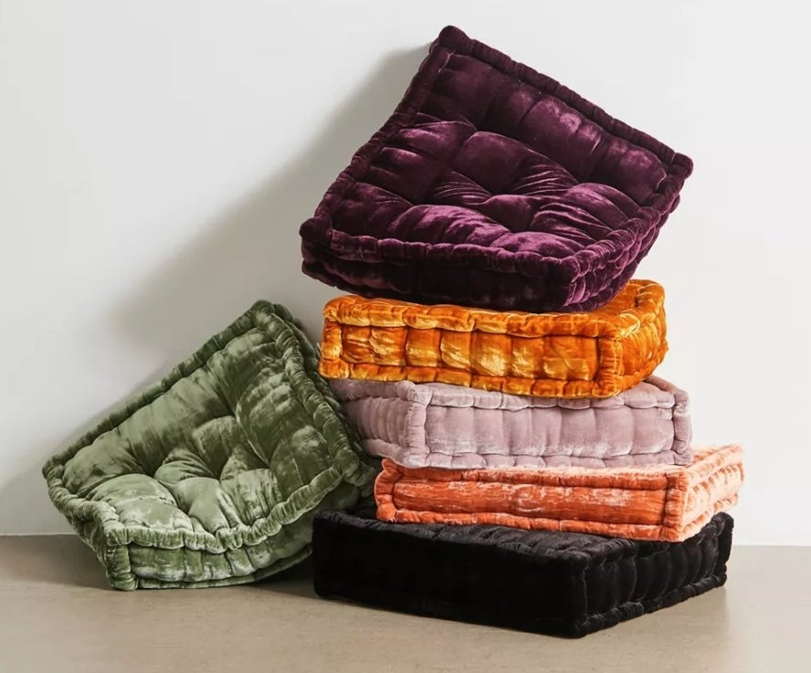 the stack of velvet floor pillows in different colors