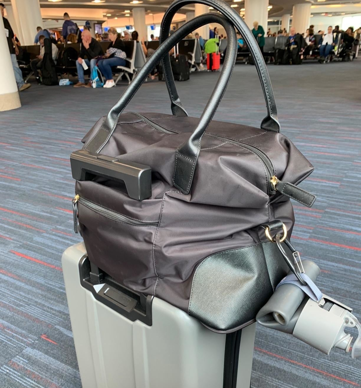 A reviewer photo of the black tote filled with things, sitting on top of a luggage