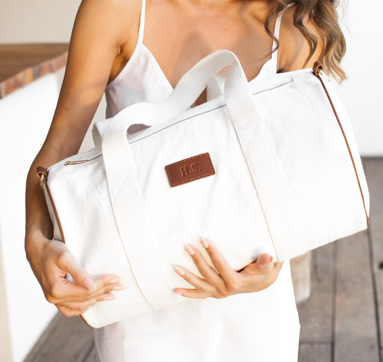 Model is holding a white duffel bag with a leather monogrammed label on the front