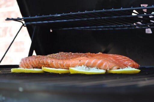 Salmon grilling on a bed of sliced lemons.
