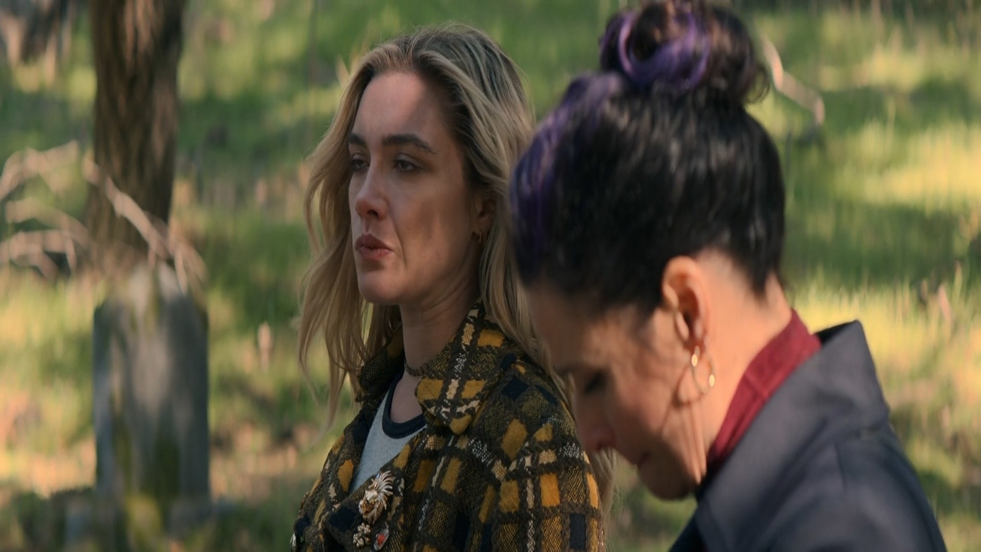 Two women standing in a graveyard.