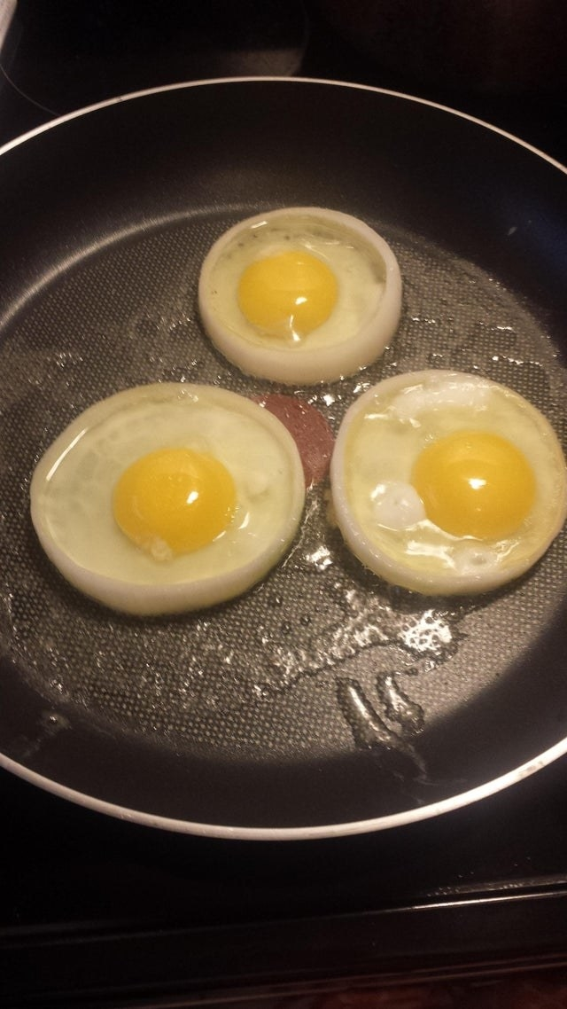 Three eggs cooking inside of onion rings.