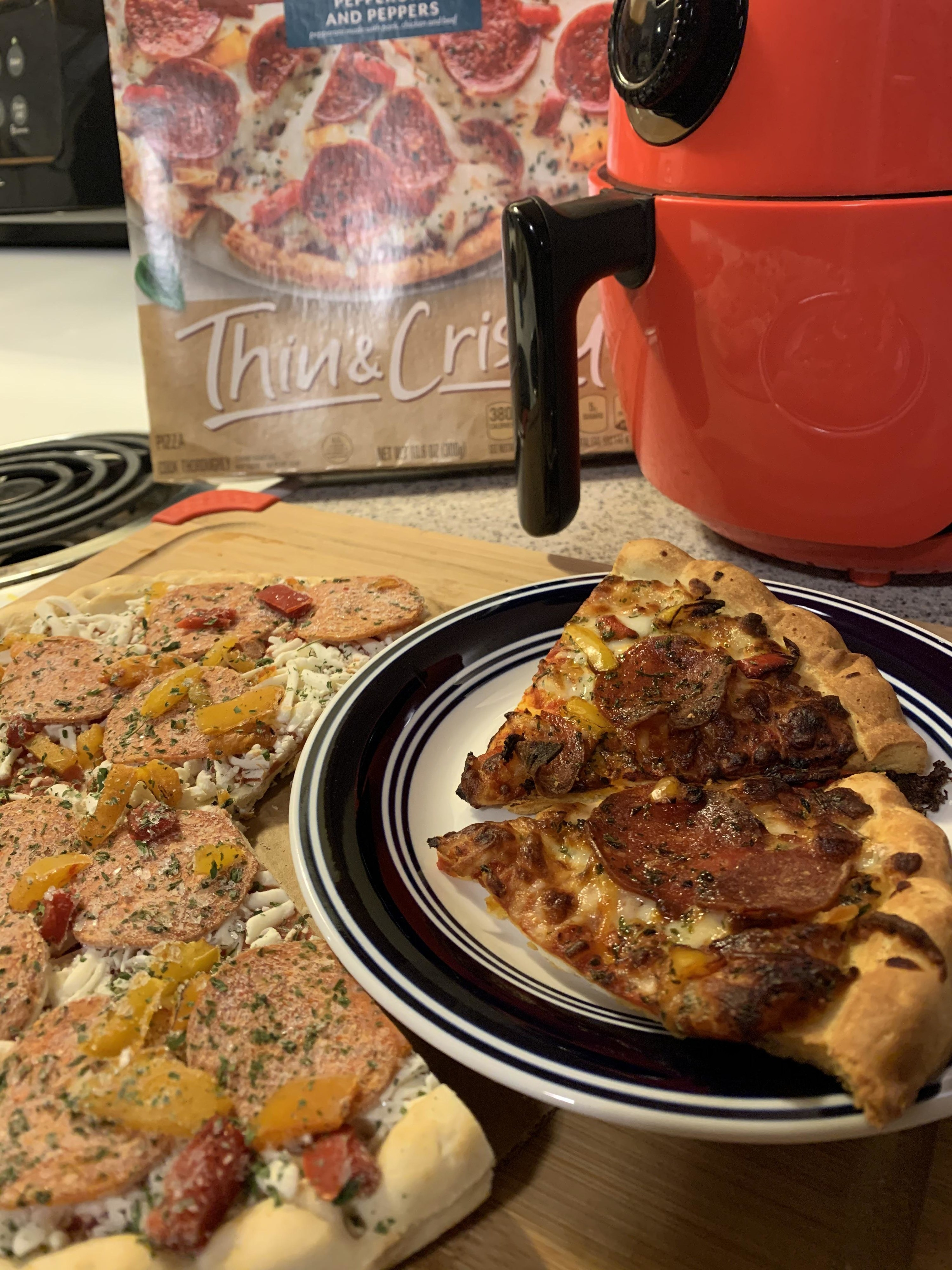 Frozen pizza and two slices that were heated up in the air fryer.