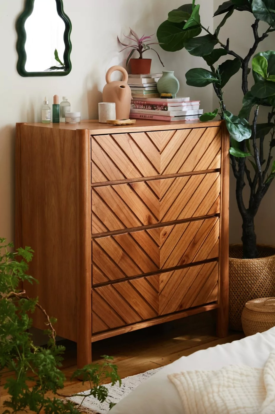 the four drawer light wood dresser with chevron patterns carved into the wood