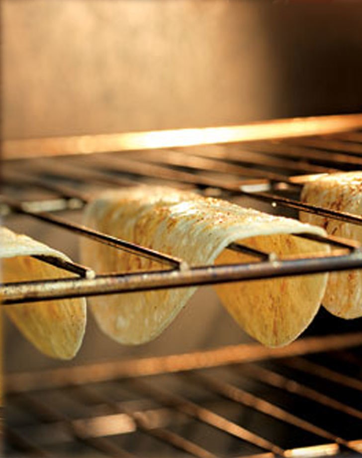 Tortillas crisping up by hanging on an oven rack.