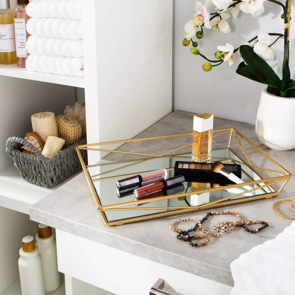Gold vanity tray with mirrored bottom holding makeup