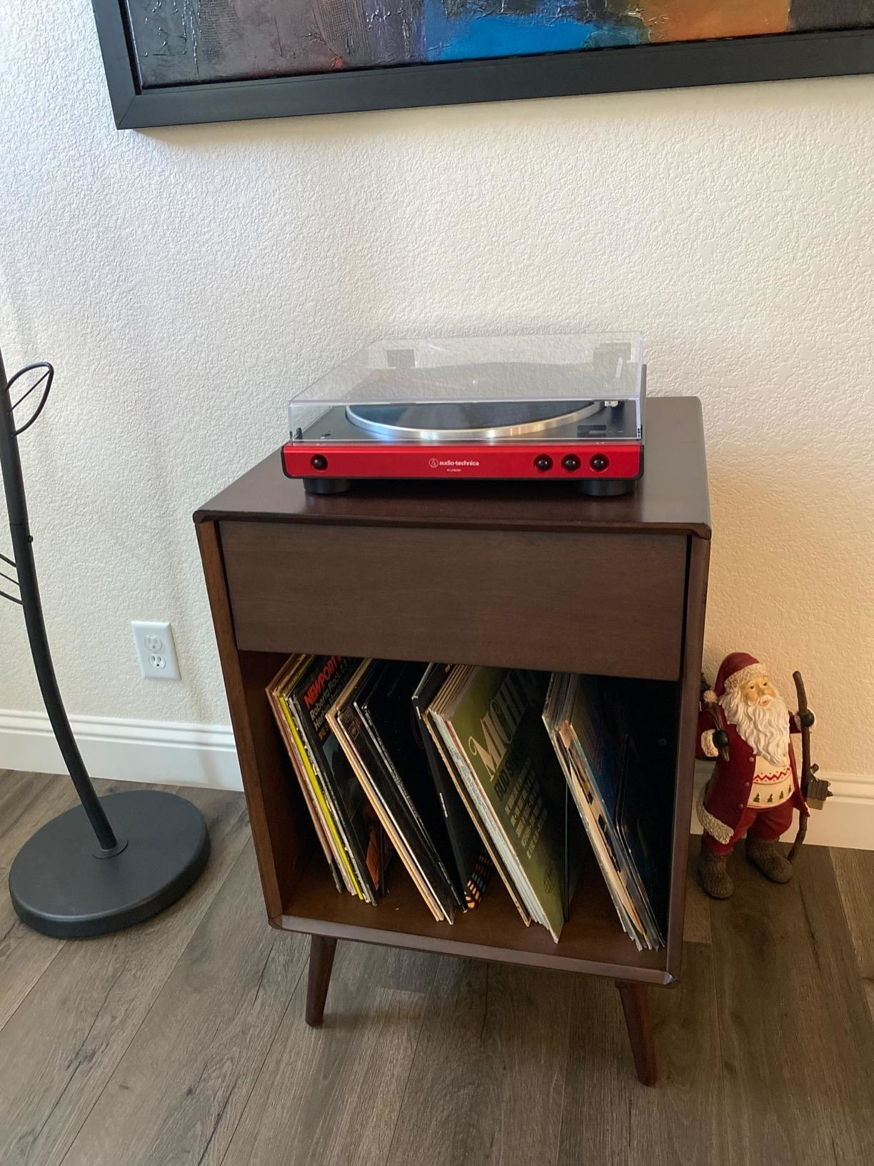 reviewer image of the black and red Audio-Technica record player on a small wooden table with record storage