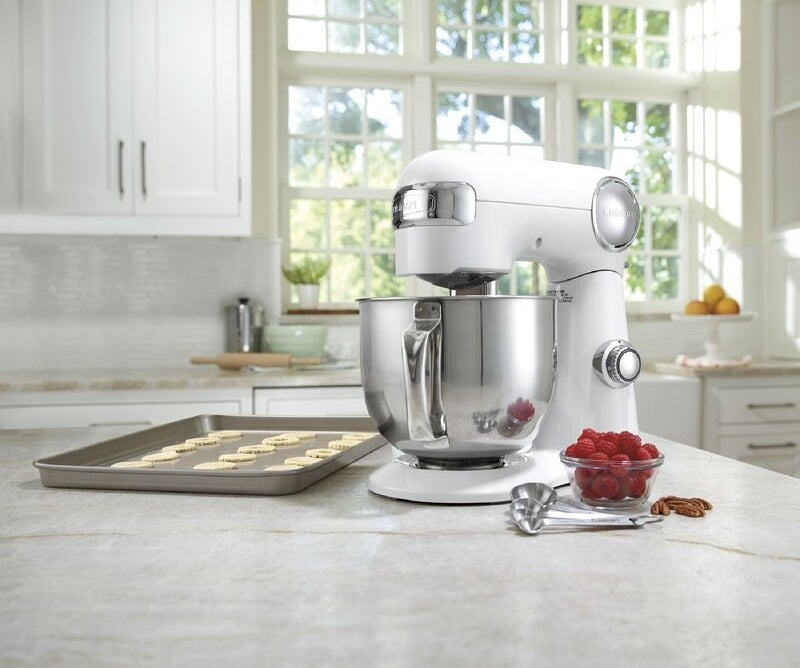 the mixer on a counter with a tray of cookies