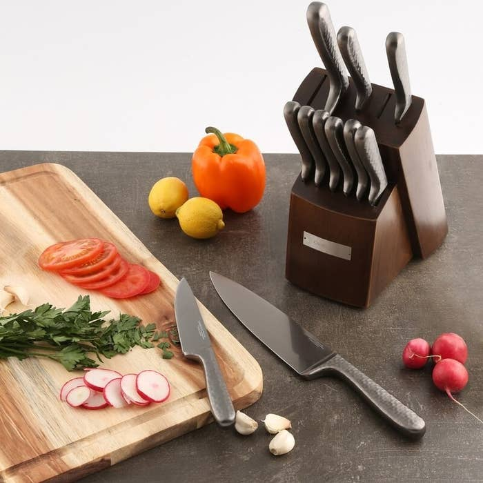 the knife set and block next to a cutting board and vegetables