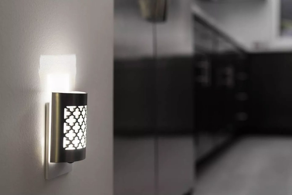 Nickel finish night light with cut out design plugged into wall