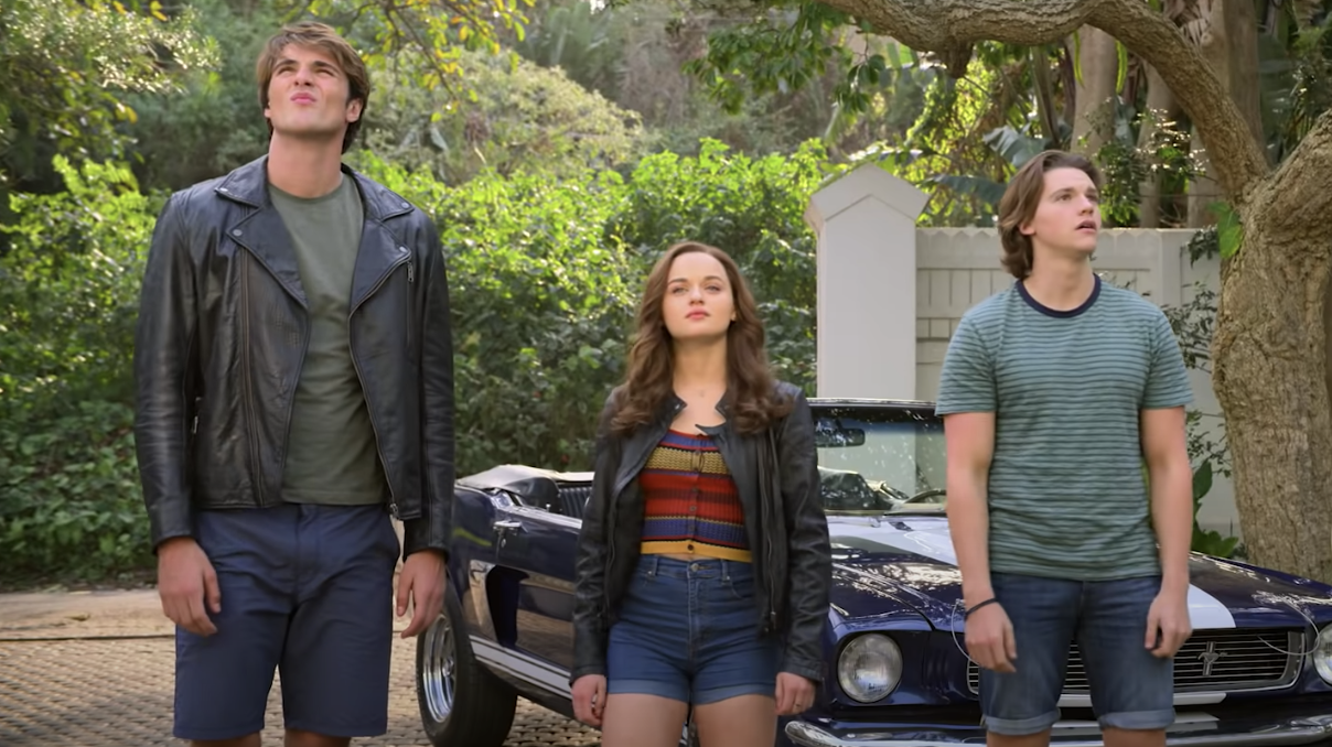Noah, Elle, and Lee standing in front of a car