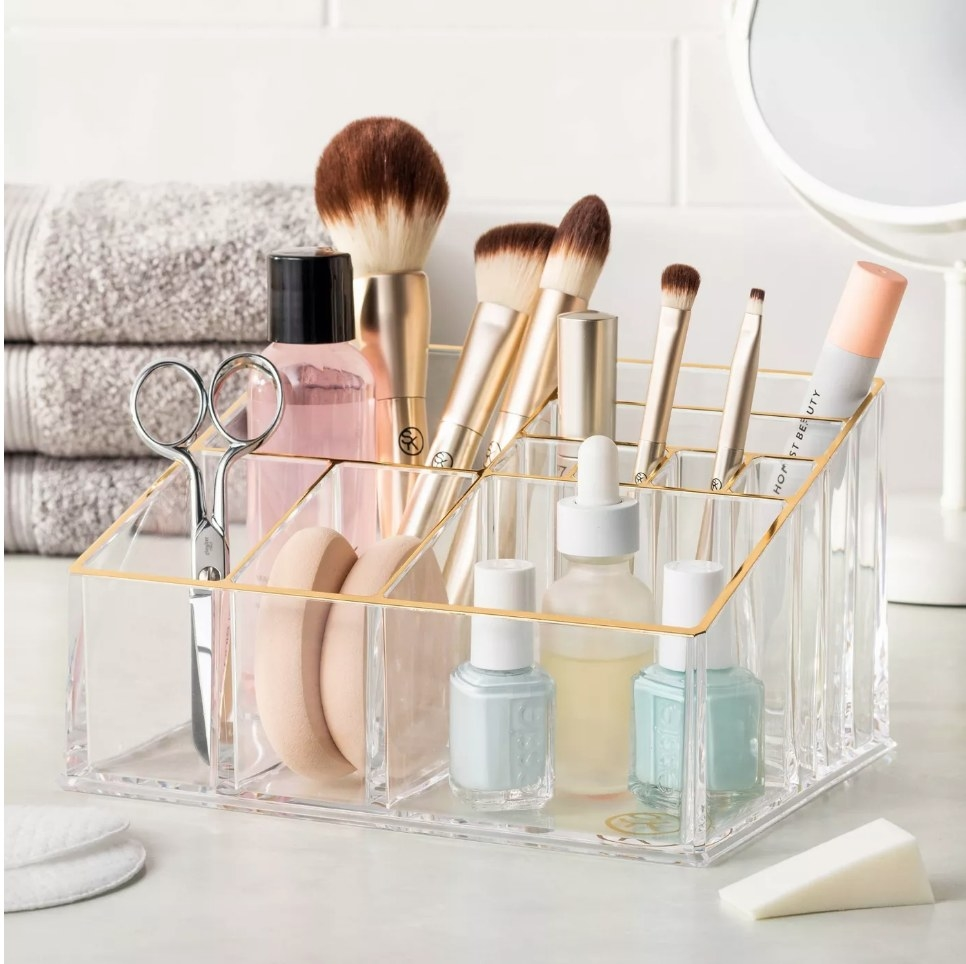 Clear makeup organizer with gold trim on the border, filled with brushes, nail polish, scissors and makeup