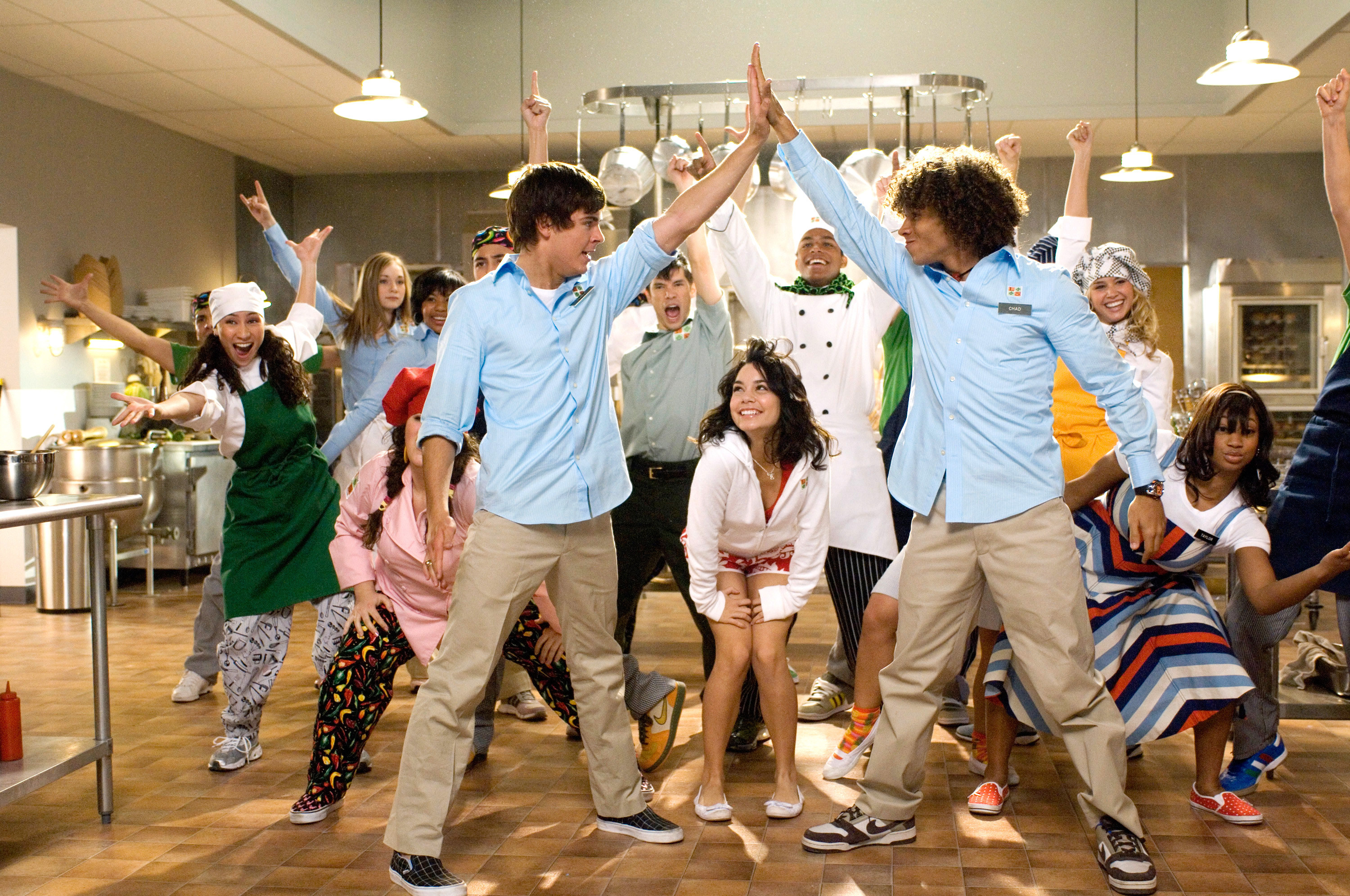 cast of high school musical dancing and singing in a kitchen