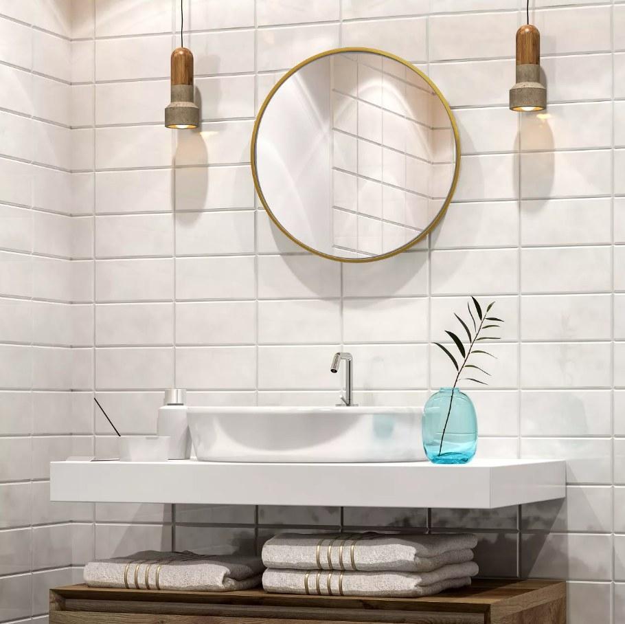 Brass round wall mirror over bathroom sink