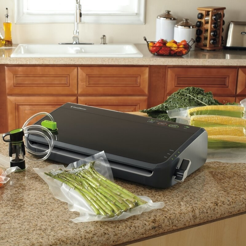 the foodsaver with a bag of asparagus on a counter