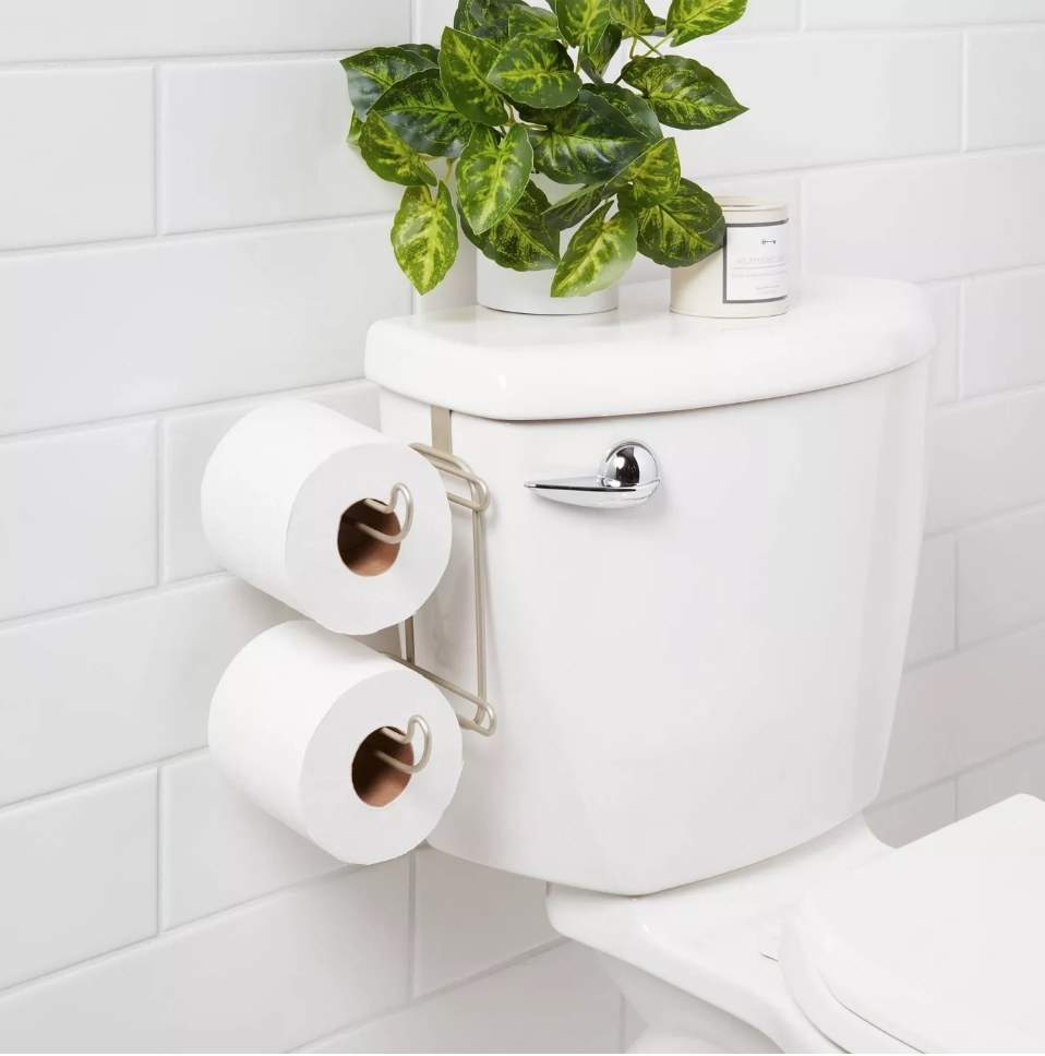 Double roll toilet paper holder attached to tank of white toilet