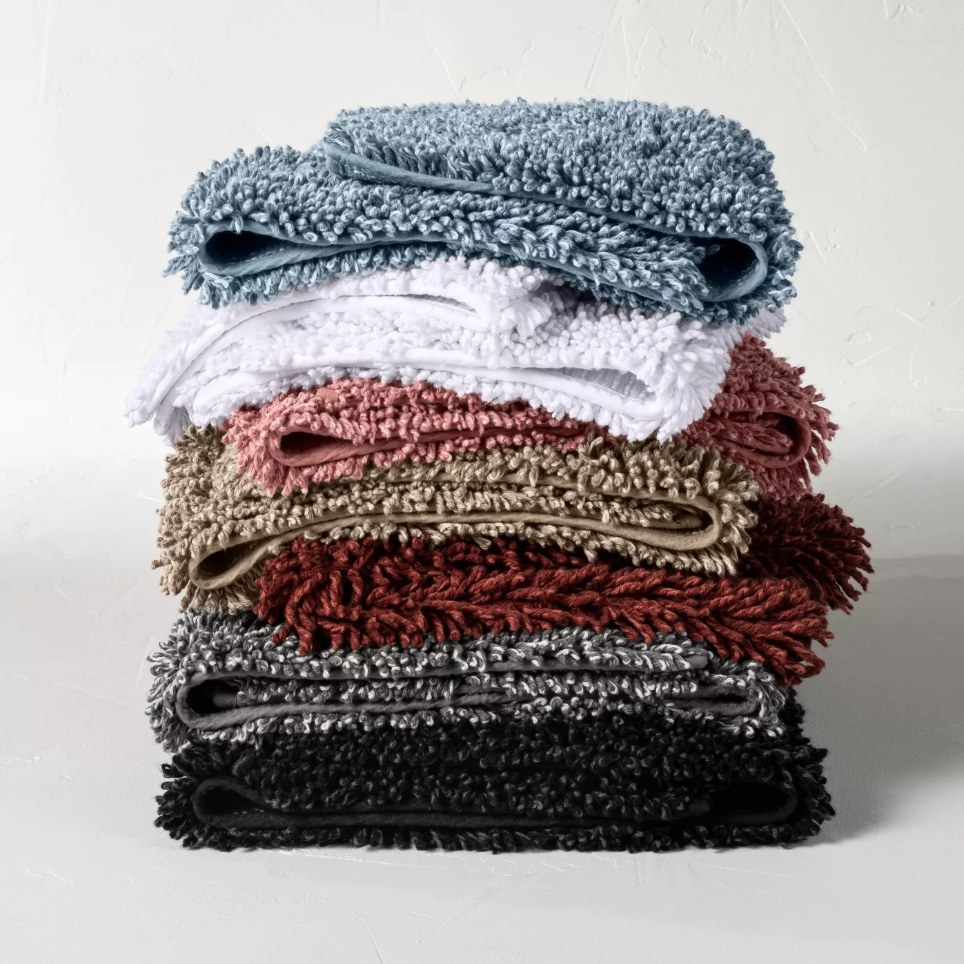 Stacked bath rugs, blue, white, pink, brown, red, gray and black