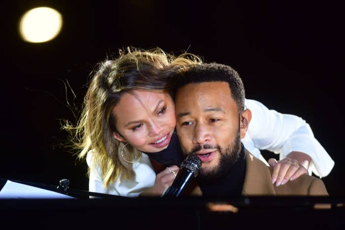 Chrissy leaning over her husband while he sings at the piano