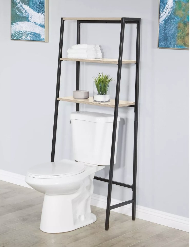 Three shelf etagere over toilet with black hardware and light wood shelving
