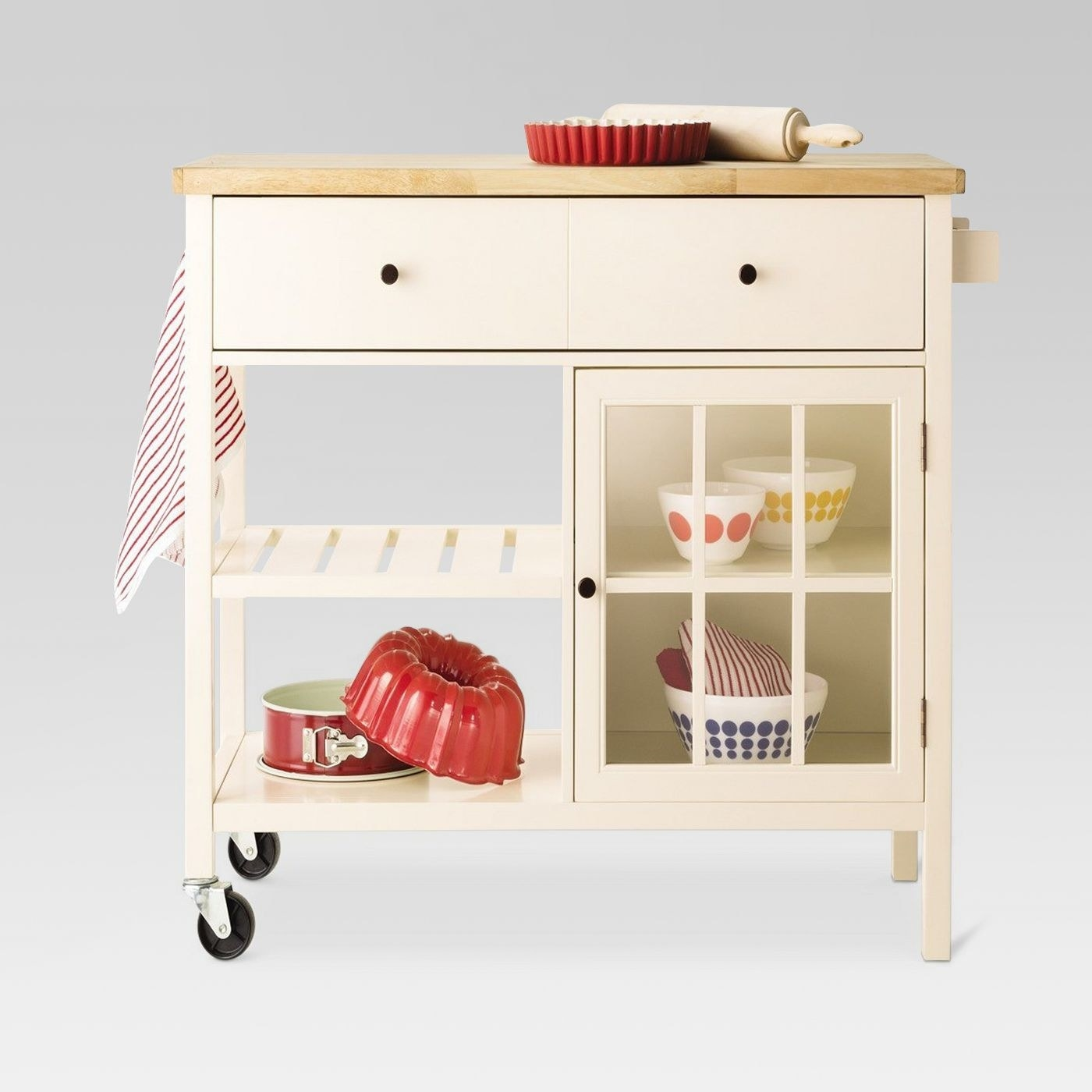 white kitchen island with 2 wheels, drawers, shelves, and a wood top