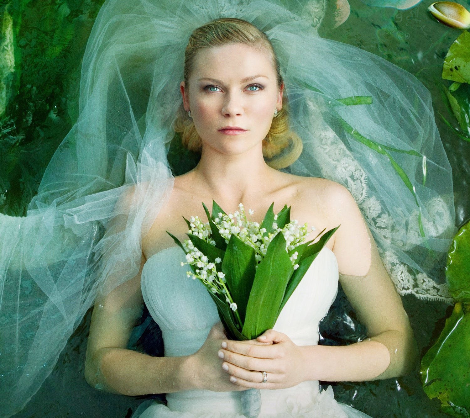 Dunst looking sad in a stunning wedding gown in the movie melancholia