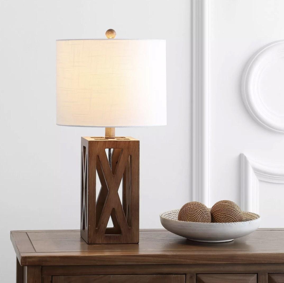 A wooden lamp with an open, rectangular body