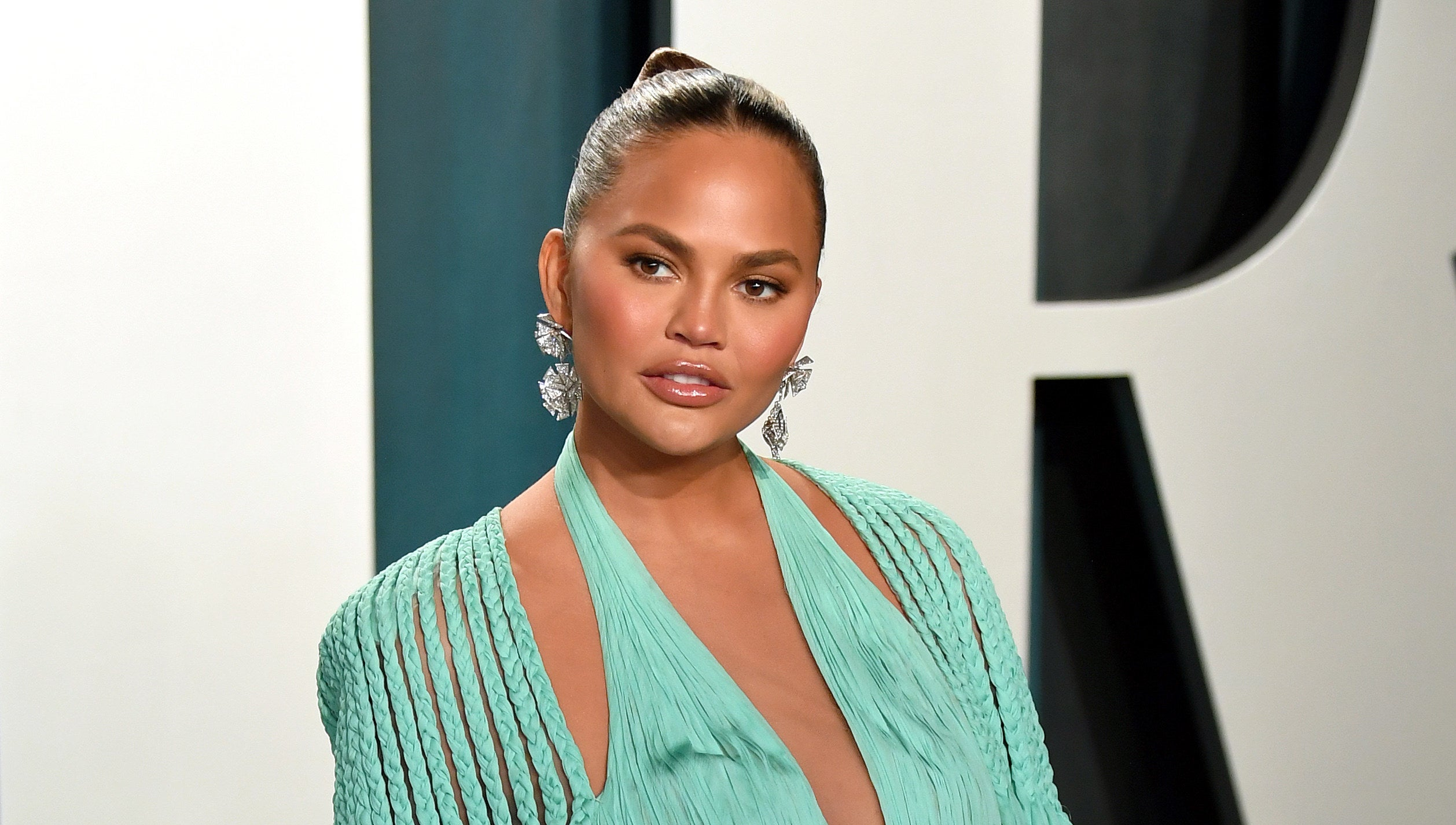 Photo of Chrissy Teigen in a seafoam green dress looking at something off-camera