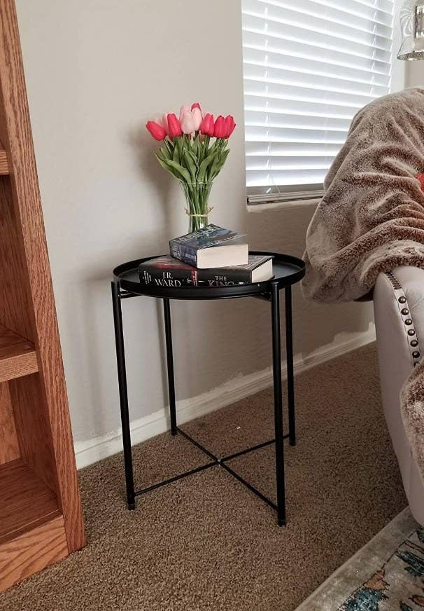 A black, metal side table with a round removable tray atop