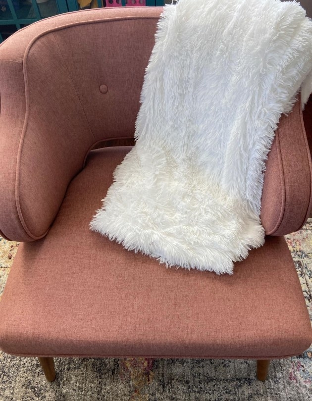 A white, faux fur throw blanket draped over an accent chair