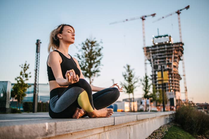 Young adult woman sitting on the ground in the public park meditating next to a construction site