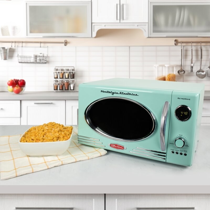 the aquamarine microwave on a counter with macaroni and cheese