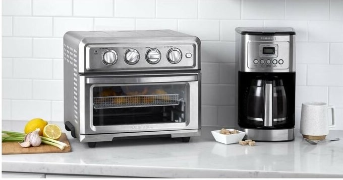 the stainless steel toaster oven on a counter next to seasonings and a coffee maker