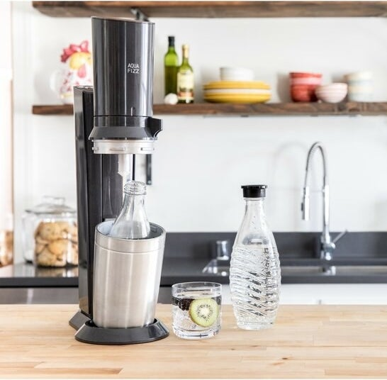 the sodastream on a counter with a glass