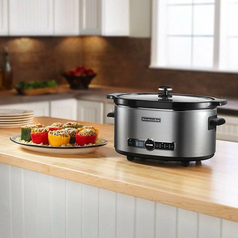 the slow cooker on a counter next to a plate of food