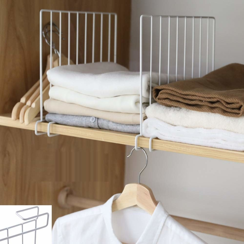 A shelf divider attached to a shelf inside a cupboard with clothes neatly arranged